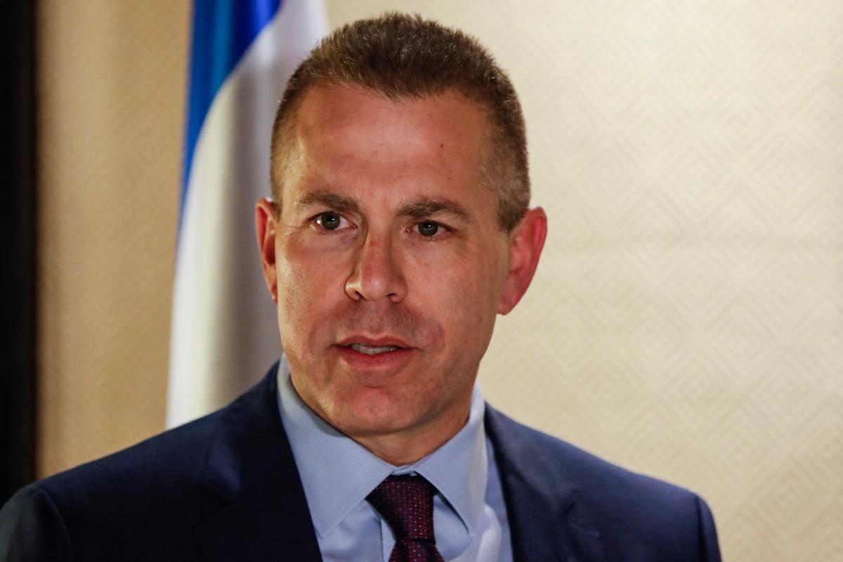 rostro del ministro girado hacia la izquierda de la imagen, viste traje y corbata azules, camisa celeste, la bandera de Israel se adivina detrás